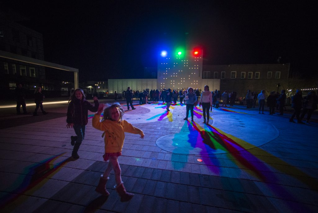 Kids having fun with the multi-color shadows cast by the stage lights in Argenta Plaza.